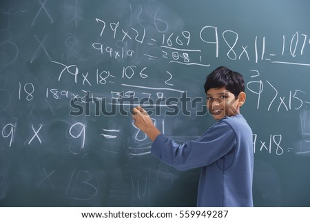 boy working at chalkboard, smiling at camera