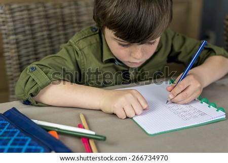 boy working hard on his homework, shallow depth of field - stock photo