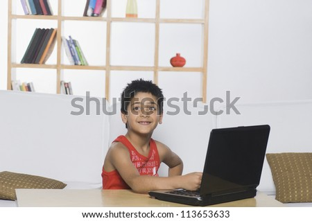 Boy working on a laptop and smiling