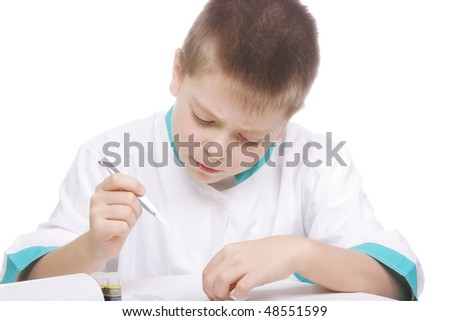 Boy working with tweezers sitting at table against white