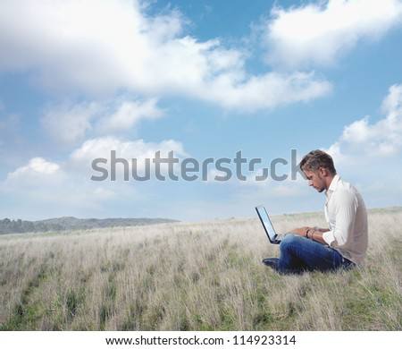 Boy works in a field with laptop - stock photo
