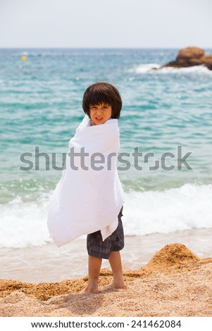 boy wrapped in a white towel on the beach