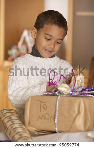 Boy wrapping gift for mom - stock photo