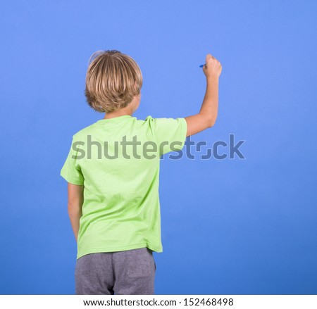 boy writes a pencil in space, standing with his back to the viewer - stock photo