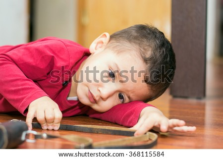 boy 2 years lying on the floor playing
