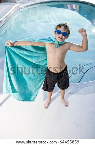 Boy, 9 years, playing by swimming pool in pretend superhero costume flexing muscles - stock photo