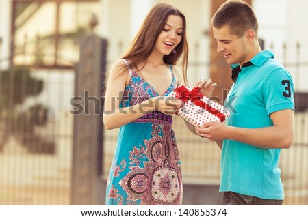 boyfriend a gift girl. man presented a surprise to woman - stock photo