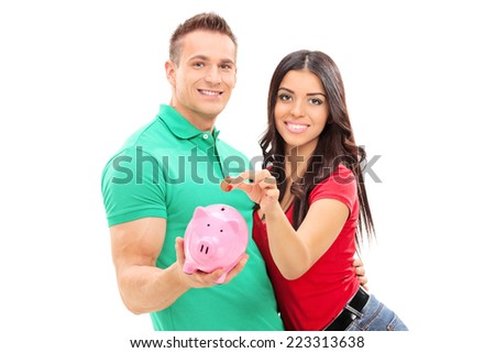 Boyfriend and girlfriend inserting money into a piggybank isolated on white background - stock photo
