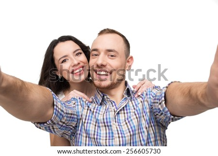 Boyfriend and girlfriend making photo on phone. They look happy. Isolated on white background