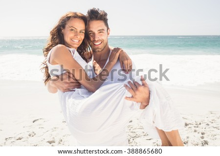Boyfriend carrying his girlfriend on the beach