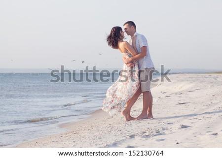 Boyfriend hugging his girlfriend on the beach - stock photo