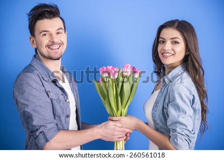 Boyfriend is giving flowers to his beautiful girlfriend isolated on blue background. - stock photo
