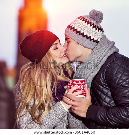 Boyfriend kisses his girlfriend. Young couple in love share hot drink in red cup. Two youngsters dating on Valentine's day.