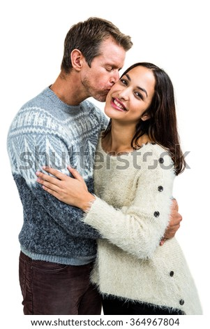 Boyfriend kissing girlfriend while embracing against white background - stock photo