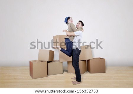 Boyfriend lift girlfriend at new home surrounded with boxes