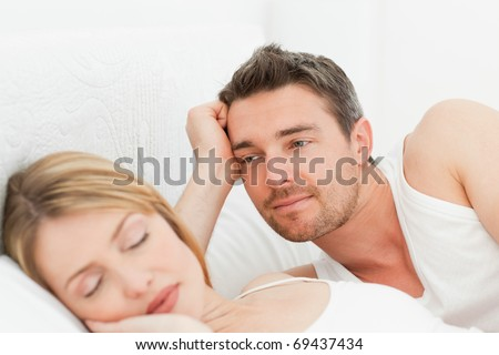 Boyfriend looking at his girlfriend who is  sleeping - stock photo
