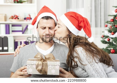 boyfriend looks skeptical to his christmas gift while his girlfriend give him a kiss - stock photo