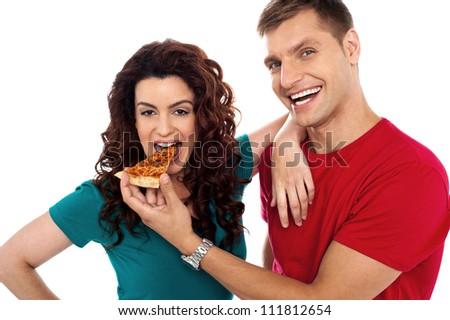 Boyfriend making her girl eat hot pizza piece. Both having fun - stock photo
