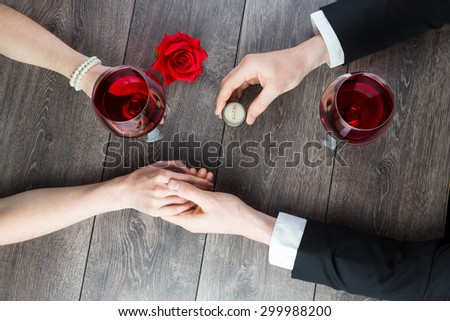 Boyfriend requesting hand of his girlfriend with a engagement ring in a restaurant. Top view. Elegant candlelight dinner - stock photo