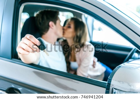 Boyfriend showing car key and kissing his girlfriend while sitting in a new car