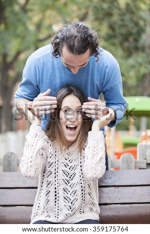 Boyfriend surprising girlfriend by covering eyes. Happy couple smiling and making guess who gesture - stock photo