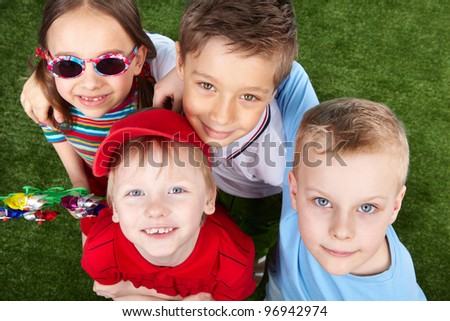 Boys and a girl looking up at camera, girl wearing sunglasses and holding a vane - stock photo