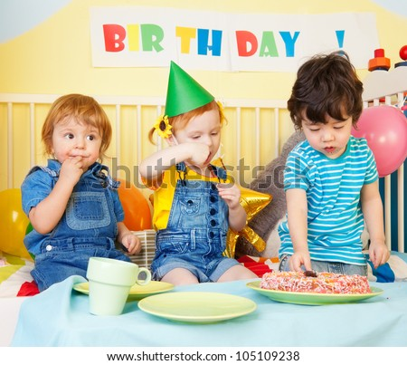 Boys and girl at the birthday party eating cake - stock photo