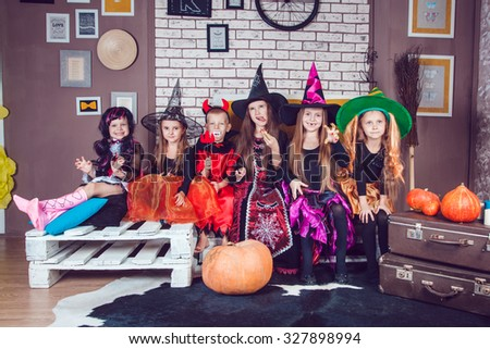 Boys and girls, dressed up in Halloween costumes, show emotions of witches and vampires. Halloween party with group children. - stock photo