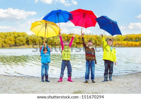 Boys and girls holding umbrellas high above - stock photo
