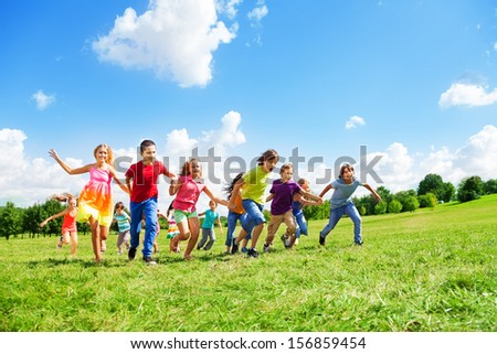 Boys and girls in large group running in the park on sunny summer day in casual clothes - stock photo