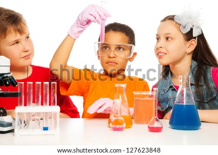 Boys and girls learning chemistry and conduct experiments - stock photo
