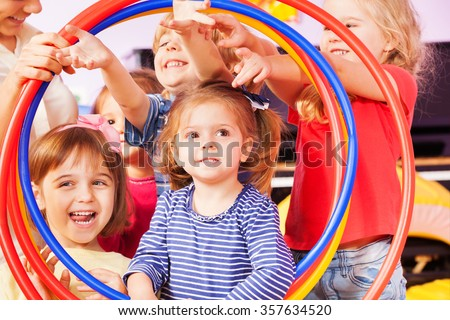 Boys and girls look though hoops - stock photo