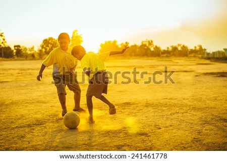 boys are playing football in the sunshine day - stock photo