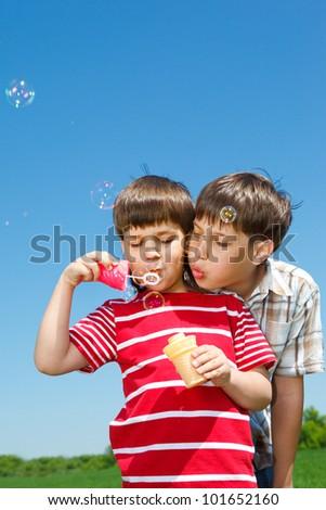 Boys blowing bubbles against blue sky - stock photo