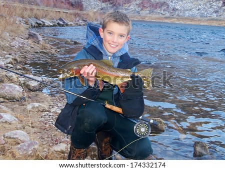 Boys fly fishing - handsome young man next to a river holding a large Rainbow Trout he caught fly fishing - stock photo