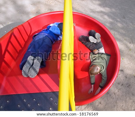 Boys go for a drive on the equipment of a playground - stock photo