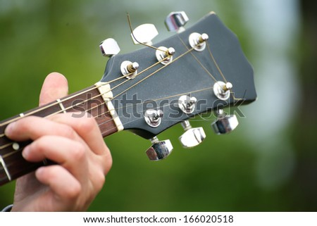 boys hand with a guitar - stock photo