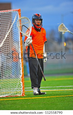 Boys High School Varsity lacrosse goalie stands guard to protect his gate from the opponents. - stock photo