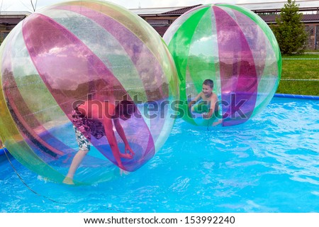 Boys in a balls on the water. Water Zorbing - stock photo