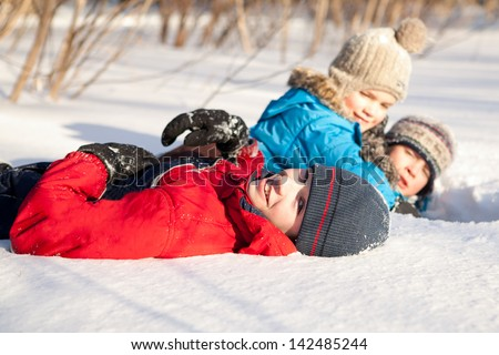 boys in winterwear laughing while playing in snowdrift outside - stock photo