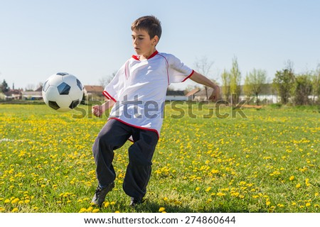 Boys kicking football on the  field