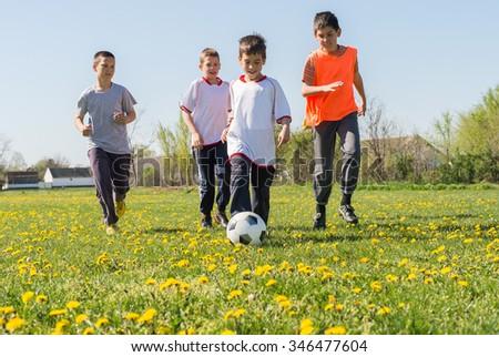 Boys kicking football on the  field - stock photo