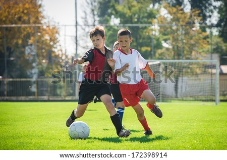 boys  kicking football on the sports field - stock photo
