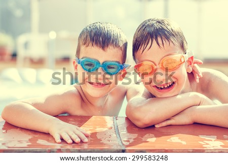 Boys laughing in pool, vintage style - stock photo
