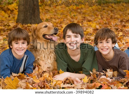 Boys Laying Down with the Dog in the Fall Leaves - stock photo