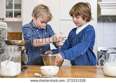 Boys mixing dough in a bowl using a whisk during a baking workshop for kids at a birthday party - stock photo