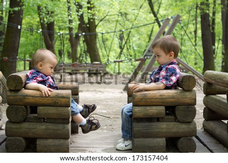 Boys on a wooden train in a park - stock photo
