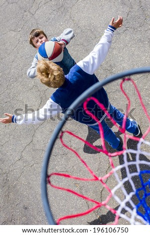 boys playing basketball photographed from above the ring - stock photo
