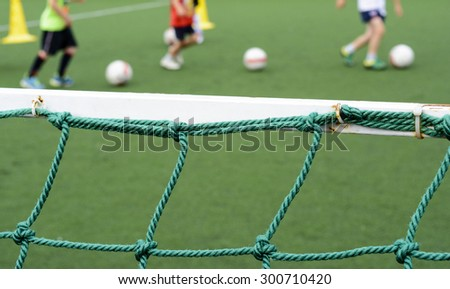 Boys playing football on the sports field in the background - stock photo
