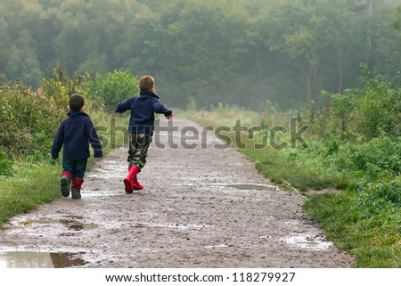 Boys playing in a muddy puddle